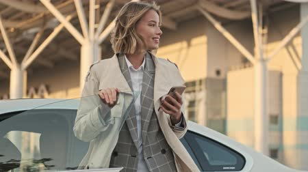 em pé : Cheerful blonde business woman in coat using smartphone and looking away while standing near the car on airport parking outdoors