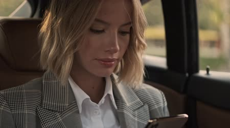 job transfer : Close up view of Smiling blonde business woman in coat using smartphone while sitting in car Stock Footage