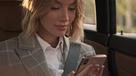 job transfer : Close up view of Happy blonde business woman in coat using smartphone and looking away while sitting in car Stock Footage