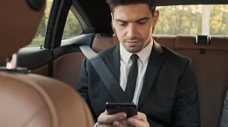 job transfer : Concentrated handsome businessman using smartphone while sitting in car