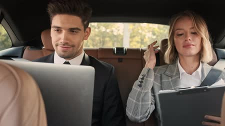 job transfer : Smiling confident business couple working with laptop computer and documents while sitting in car Stock Footage