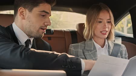 концентрированный : Close up view of confident business couple discussing about something while sitting in car Стоковые видеозаписи