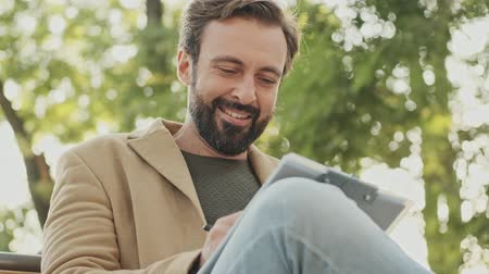aşağıda : View from below of Smiling elegant bearded man in coat writing something in clipboard and yawning while sitting in the park outdoors Stok Video