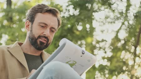 aşağıda : Pleased elegant bearded man in coat reading documents in clipboard while sitting in the park outdoors Stok Video