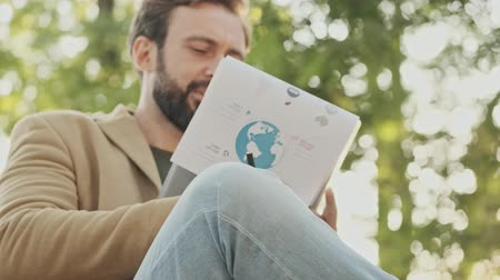 broda : Smiling elegant bearded man in coat reading newspaper while sitting in the park outdoors