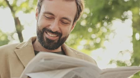 газета : Smiling pensive elegant bearded man in coat looking away while holding newspaper and sitting in the park outdoors