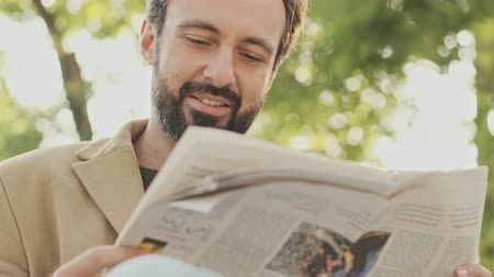 газета : Happy elegant bearded man in coat reading newspaper while sitting in the park outdoors
