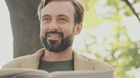 holding newspaper : Pleased elegant bearded man in coat reading newspaper while sitting in the park outdoors