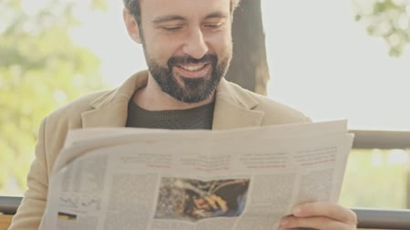 holding newspaper : Side view of Cheerful elegant bearded man in coat reading newspaper while sitting in the park outdoors