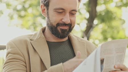 holding newspaper : Cheerful elegant bearded man in coat reading newspaper while sitting in the park outdoors