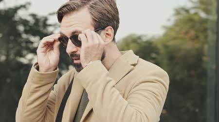 stroll : Side view of Smiling elegant bearded man in coat putting on a sunglasses and looking away outdoors Stock Footage