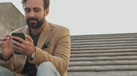 broda : View from below of pleased elegant bearded man in coat using smartphone and looking away while sitting on stairs outdoors