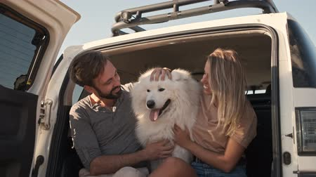 memeli : An attractive couple man and woman are petting a dog while sitting in the car trunk