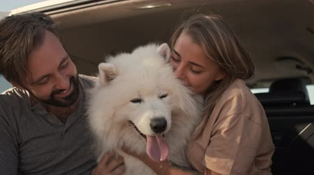 samoyedo : A happy smiling couple man and woman are petting and hugging a dog while sitting in the car trunk
