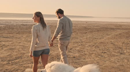 chlupatý : An attractive young couple man and woman are walking with a dog on the lake in summer Dostupné videozáznamy