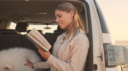 chlupatý : A pretty young woman is reading a book while sitting in the trunk with a dog outdoors in summer