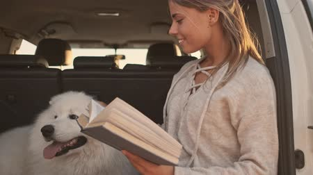 memeli : A beautiful young woman is reading a book while sitting in the trunk with a dog outdoors in summer