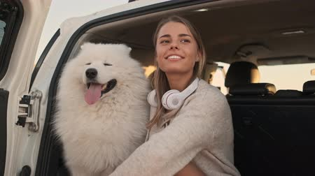 chlupatý : A smiling positive young woman is sitting with a dog in the trunk outdoors in summer