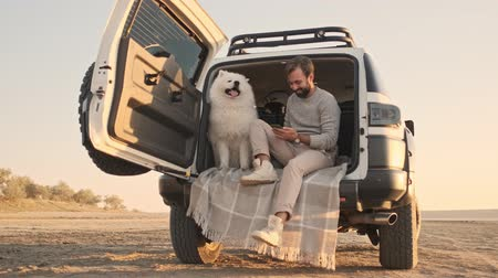 memeli : A handsome young man is sitting with a dog in the trunk while using his smartphone outdoors in summer Stok Video