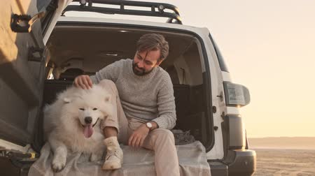 taranmamış : A young man is petting a dog while sitting in the trunk outdoors in summer