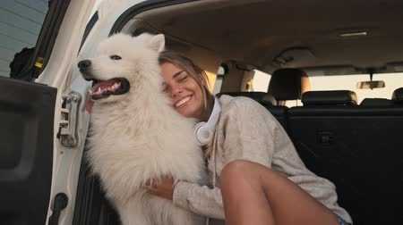 chlupatý : A smiling positive young woman is hugging and petting a dog in the trunk outdoors in summer