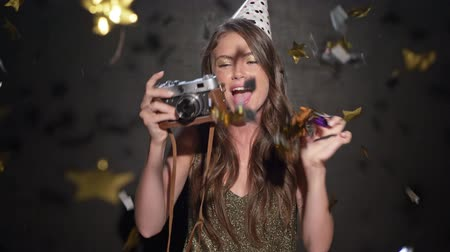 żart : A rejoicing young girl wearing a birthday cap is blowing into the tube while confetti starting to fall dawn and than taking a photo isolated over black background Wideo
