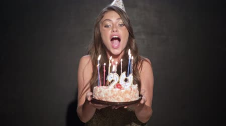 yirmi : A happy smiling young girl is holding a birthday cake and blows out the candles isolated over black background