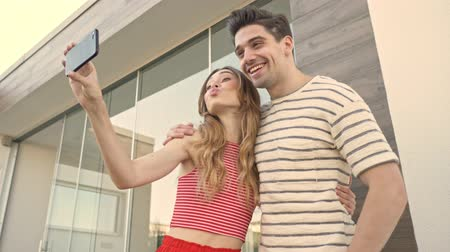 trawnik : A cheerful couple man and woman are taking selfie outdoors near the villa in summer