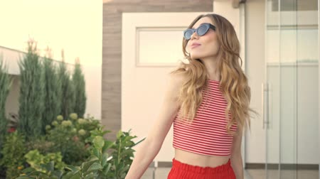 hayran olmak : A cropped view of beautiful woman in sunglasses is walking in the yard in summer