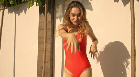 gramado : An attractive smiling young girl is dancing in the red swimsuit in the terrace in summer Stock Footage