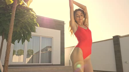 trawnik : An pretty smiling young girl is dancing in the red swimsuit outside in summer in the countryside