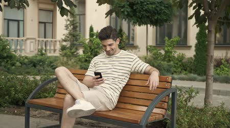 бульвар : A positive caucasian man is smiling and using cellphone while sitting on bench at city street