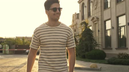 tevreden : A handsome smiling man in casual clothes and sunglasses is walking on the city street Stockvideo