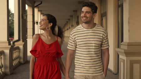 não barbeado : An attractive smiling couple is having a date while strolling near the colonnades