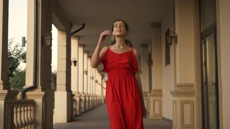 arete : A beautiful young woman in red dress is walking to the camera near colonnades