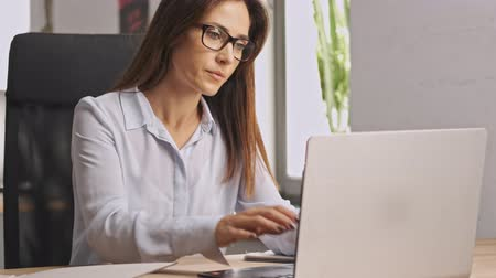 mentor : Concentrated businesswoman wearing eyeglasses working with documents and laptop computer while sitting in office