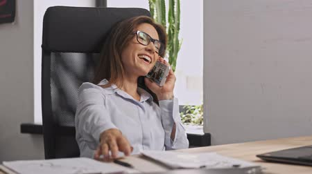mentor : Happy businesswoman wearing eyeglasses talking by smartphone and relaxing on office chair in office