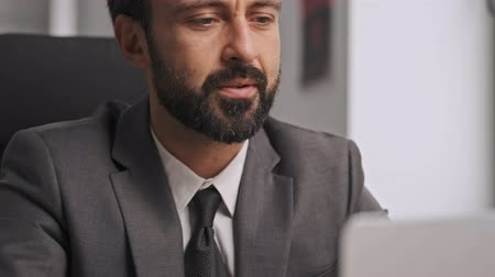 dyrektor : Focused thoughtful businessman in formal suit working with laptop computer while sitting by the table in office