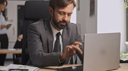barbu : Serious businessman in formal suit using laptop computer and relaxing after that while sitting by the table in office Vidéos Libres De Droits