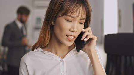 trabalhador de escritório : Smiling asian businesswoman talking by smartphone and looking away while standing in office Stock Footage