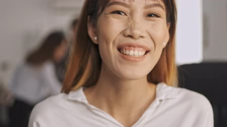 dyrektor : Close up view of Cheerful asian businesswoman laughing and looking at the camera while standing in office
