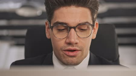 небритый : Close up view of Calm businessman in formal suit and eyeglasses using laptop computer while sitting in office