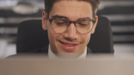 dyrektor : Close up view of Happy businessman in formal suit and eyeglasses using laptop computer while sitting in office