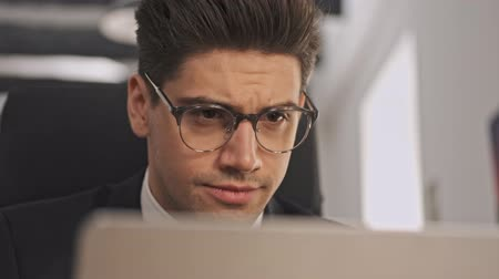 ショックを受けて : Close up view of Surprised businessman in formal suit and eyeglasses using laptop computer while sitting in office