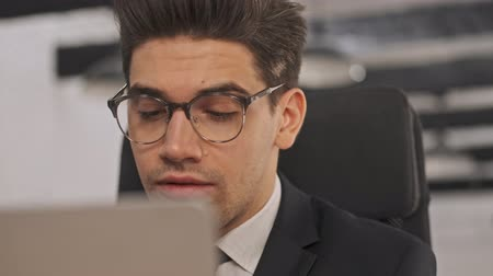 borotválatlan : Close up view of Smiling businessman in formal suit and eyeglasses using laptop computer and talking something while sitting in office