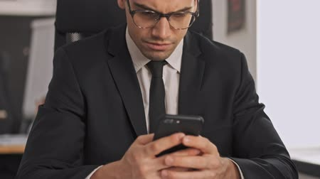 borotválatlan : Serious businessman in formal suit and eyeglasses using smartphone and looking away while sitting by the table in office