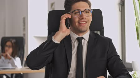carreira : Happy businessman in formal suit and eyeglasses having a call and looking away while sitting by the table in office