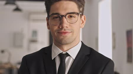 небритый : Smiling businessman in formal suit and eyeglasses looking at the camera while standing in office Стоковые видеозаписи