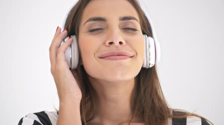 серый фон : Close up view of Pleased pretty cheerleader woman in headphones listening music with closed eyes and enjoying this moment over grey background