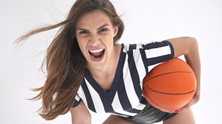 гримаса : Playful pretty cheerleader woman showing grimace while posing with ball and looking at the camera over grey background